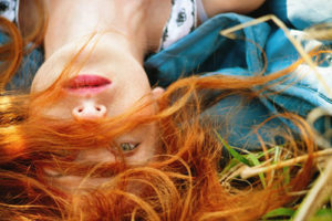 Young redheaded girl lying in a field